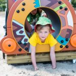 girl leaning on patterned grafic games play equipment on sand